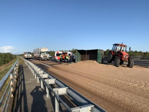 Po vilkiko ir traktoriaus su priekaba susidūrimo ant kelio pabiro grūdai