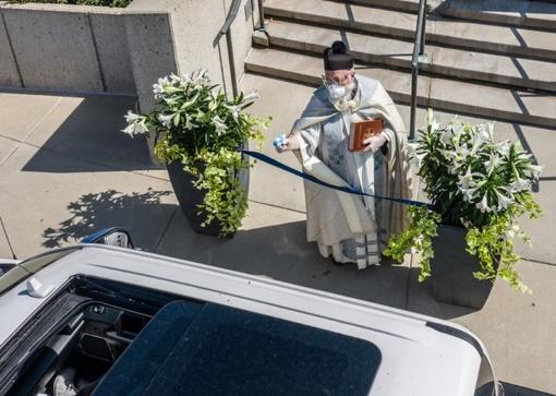 Pamaldos karantino metu: kunigas parapijiečius šventino vandens pistoletu