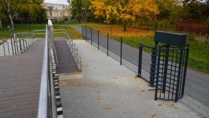 Neįgalieji vežimėliuose į pramogas parke žiūri per tvorą