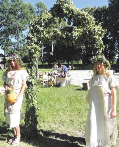Dvi jaunosios guroniškės pasitiko svečius prie stilizuotų vartų.