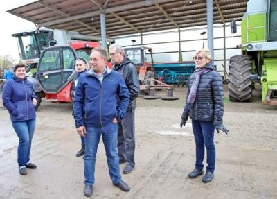 Ūkio šeimininkai Vaida ir Vigintas Ilgučiai (iš kairės) svečiams aprodo savo ūkio technikos kiemą.