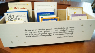 """Dovana. Aistės sesuo pasirūpino, kad iš skirtingų pasaulio kampelių atvykusios knygos turėtų jaukius namus. Jos dovana– dėžė knygoms, kurios vienoje pusėje– """"Mažojo princo"""" iliustracija, o kitoje– citata iš kūrinio."""