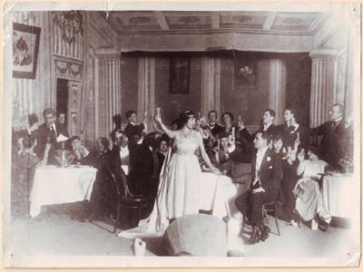 """Opera. Dž. Verdžio """"Traviata"""". Centre stovi Adelė Galaunienė (Violeta), šalia sėdi Kipras Petrauskas (Alfredas)."""