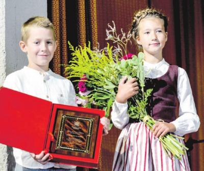 Premijos ženklas ir gėlės laureatui.