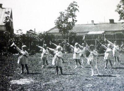"""Nuotraukos reverse užrašas: """"Mažų vaikelių gimnastika. 1932 m."""" (Irenos Rudzinskienės archyvo nuotr.)"""