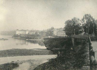 Už tilto per Vilnią matyti du kareivinių korpusai. Pirmasis - dabartinių Istorijų namų pastatas. Apie 1905 m. – Fotografas Tiburcijus Chodzka. Lietuvos nacionalinis muziejus-1
